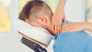 Masseur masseert nek en schouder met twee handen
