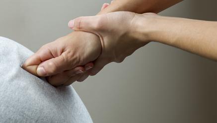 De rug wordt met de knokkels van een hand gemasseerd.